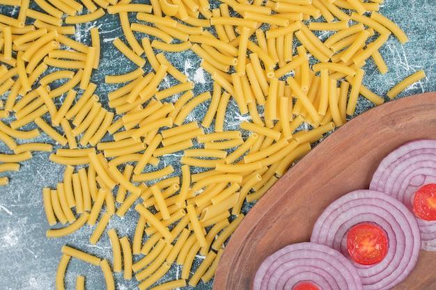 Сырые макароны с ломтиками лука и маленькими помидорами на мраморном пространстве.