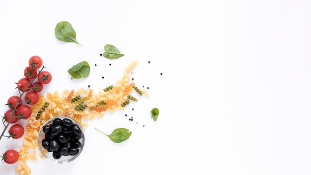 Raw pasta with tomato; black olives; with basil leaf