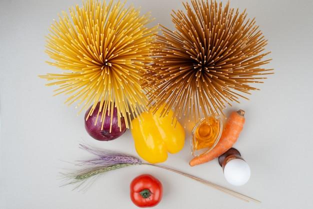 Сырые макароны с овощами на белом фоне. фото высокого качества
