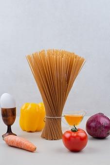 Сырая паста с овощами на белой поверхности