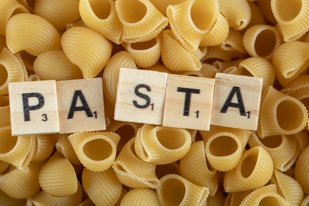 Raw pasta with wooden letters.