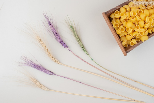 Raw pasta on wooden plate with colorful ears of wheat