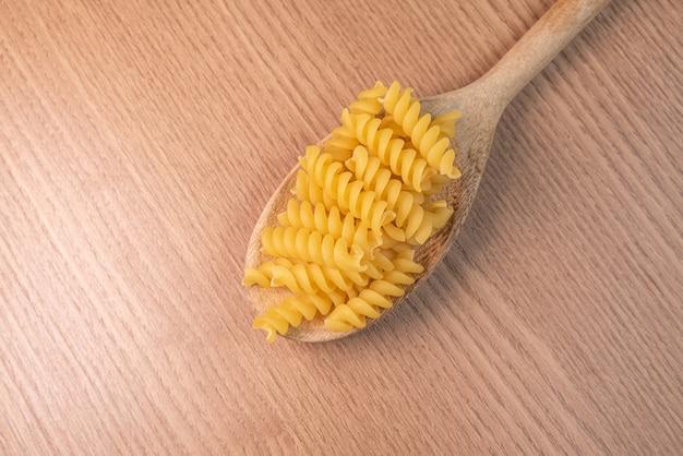 Pasta cruda in cucchiaio di legno sulla tavola di legno