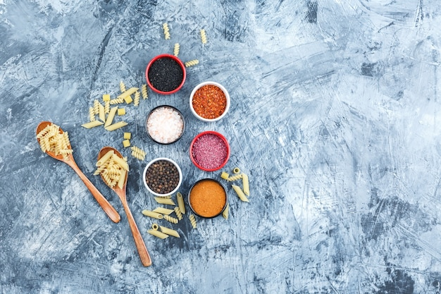 Raw pasta in wooden spoons with spices top view on a grey plaster background