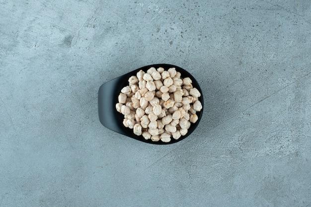 Сырые гороховые бобы в черной чашке. фото высокого качества