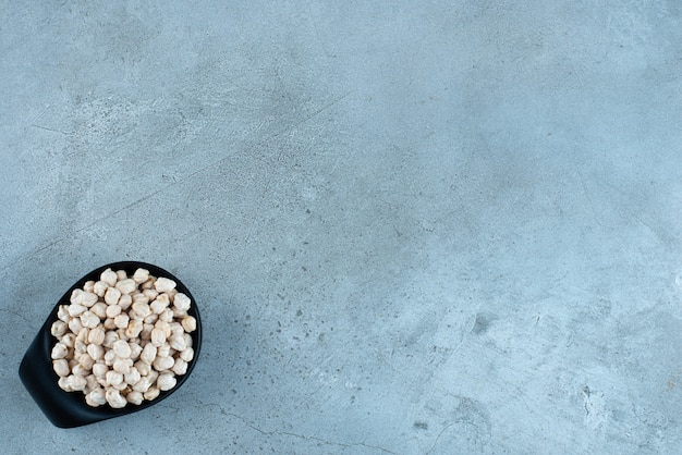 青い背景の上の黒いカップの生のエンドウ豆。高品質の写真
