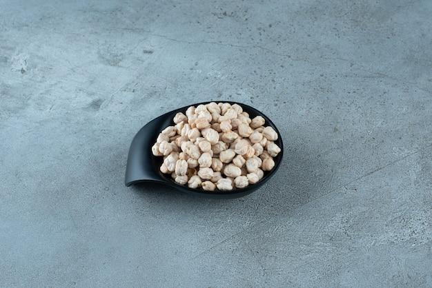 Сырые гороховые бобы в черной чашке на земле. фото высокого качества