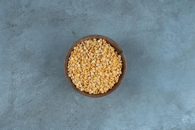 青い背景のカップに生のエンドウ豆。高品質の写真