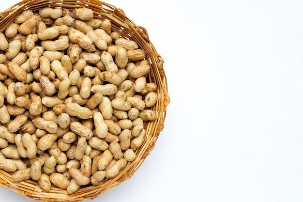 Сырые арахисы в бамбуковой корзине на белом фоне.