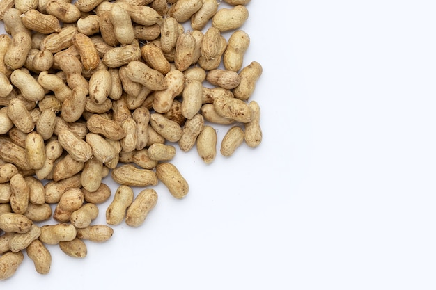 Сырые арахисы на белой предпосылке.
