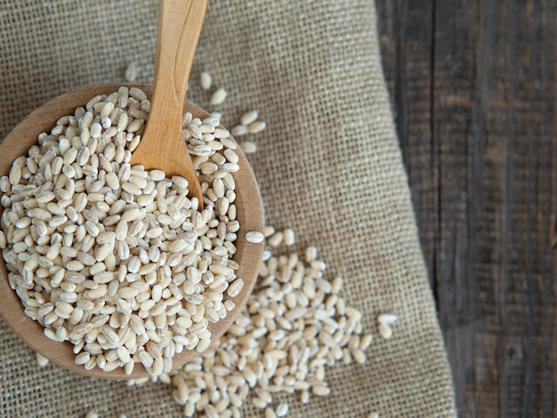 Raw pearl barley in a wooden plate and a wooden spoon next to it, spilling on a dark wooden table