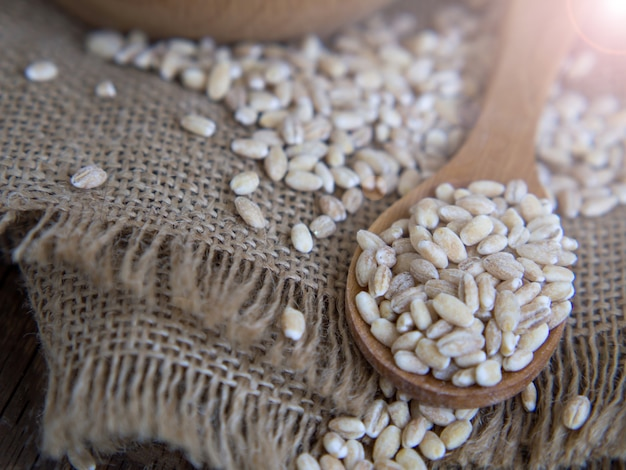 Raw pearl barley in a wooden spoon spilling on an old wooden table