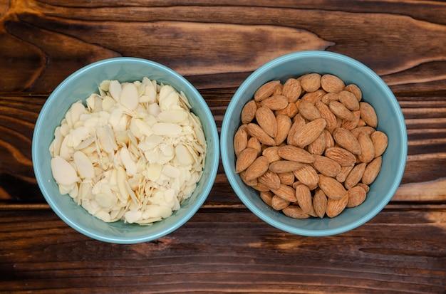 Сырой очищенный миндаль в блюдцах и миндальных лепестках для кондитерских изделий