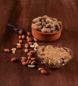 Raw and peeled peanuts in bowl and peanut butter on wooden brown background
