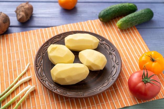 야채와 함께 식탁에 접시에 원시 껍질을 벗긴 감자 괴경. 요리를 위한 준비.