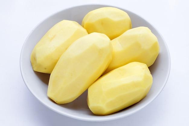Raw peeled potatoes in white bowl on white background