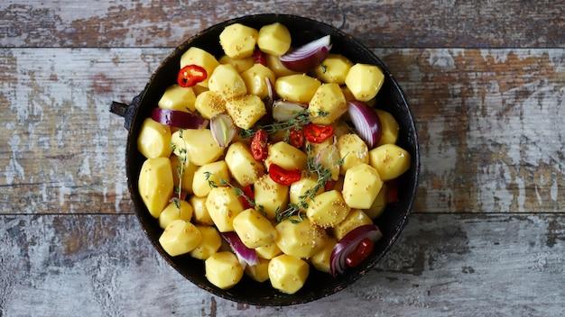 焼く前に、生の皮をむいたジャガイモ全体を、スパイス ハーブとニンニクと一緒に鍋に入れます。