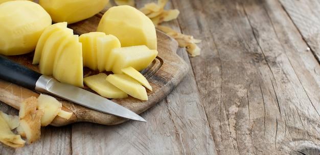 木の板にナイフで生の皮をむいたジャガイモ