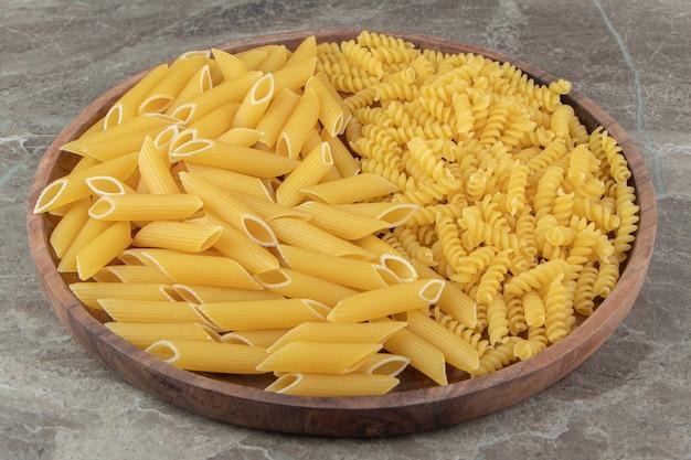 Сырые макароны пенне и фузилли на деревянной тарелке.