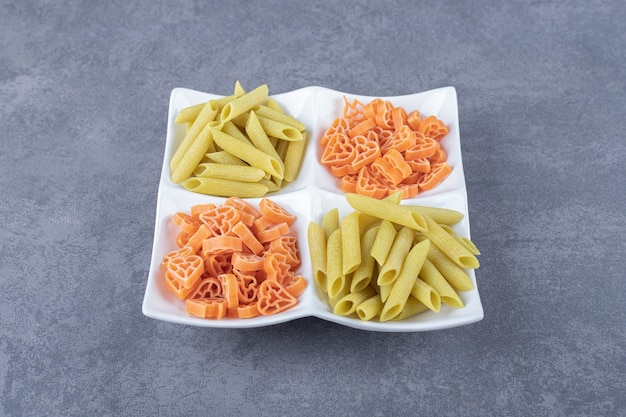 Raw penne and heart-shaped pasta on white plate.