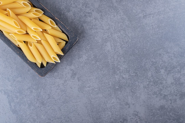 Raw penne pasta on black plate.