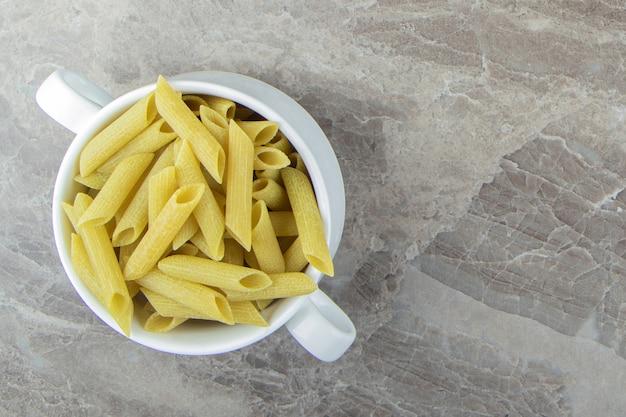 Сырая паста пенне в белой кружке