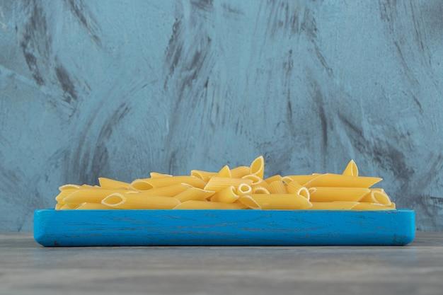 Сырые макароны пенне на синей тарелке