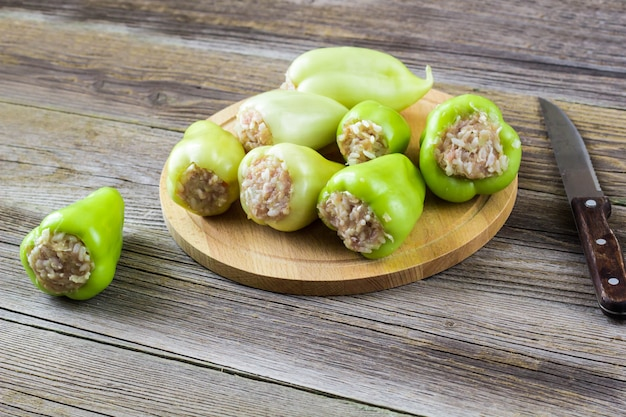 Raw peppers stuffed with meat on a wooden cutting board