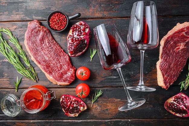 로즈마리, 매운 칠리 오일, 석류, 레드 와인 한 잔을 곁들인 생 피칸하 쇠고기 스테이크는 오래된 짙은 나무 탁자 위에 있습니다.