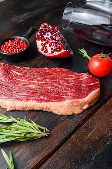Raw picanha beef steak with rosemary, spicy chili oil, pomegranate on old dark wooden table side view.