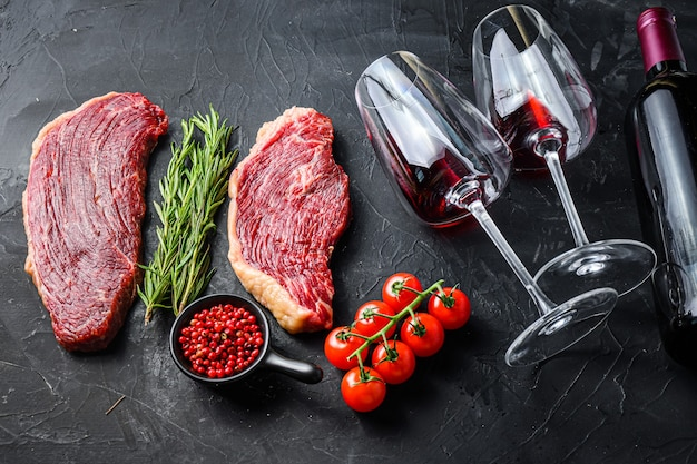 Raw picanha steaks with seasonings and herbs near bottle and glass of red wine, over black textured table side view.