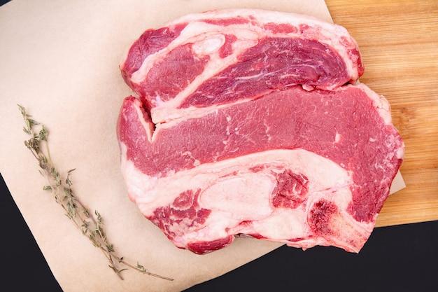 Сырой кусок говяжьего стейка на деревянной разделочной доске с травами и специями. свежие ингредиенты для ресторанов. мясо на кости.