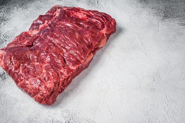대리석 쇠고기 양지머리 고기의 원시 조각입니다. 흰 바탕. 평면도. 공간을 복사합니다.