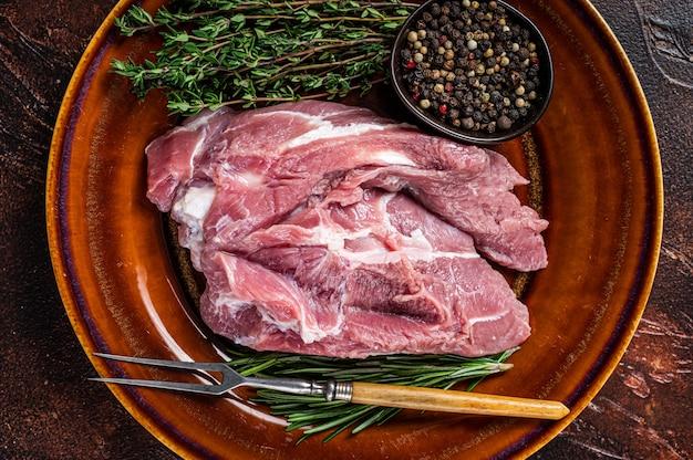Сырой кусок свиной лопатки со специями на деревенской тарелке