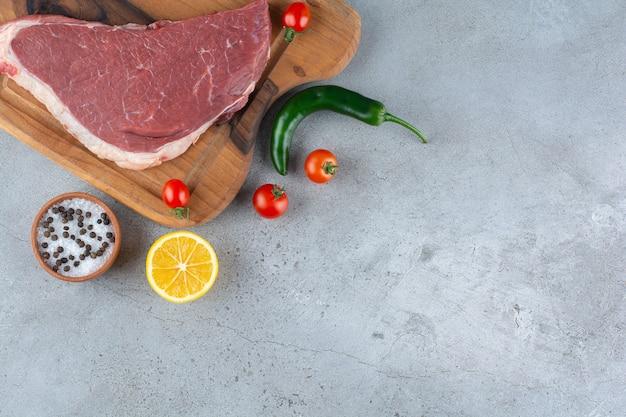 Сырой кусок красного мяса на каменном столе.