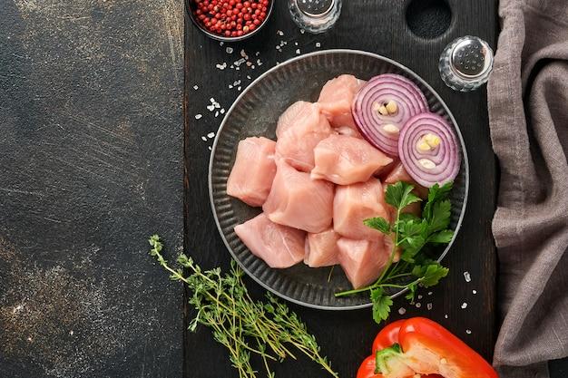 어두운 회색 배경에 나무 판자, 향신료, 허브, 야채에 있는 닭고기의 원시 조각 고기 재료. 굴라시 또는 시시 케밥의 원료. 평면도. 무료 복사 공간입니다.
