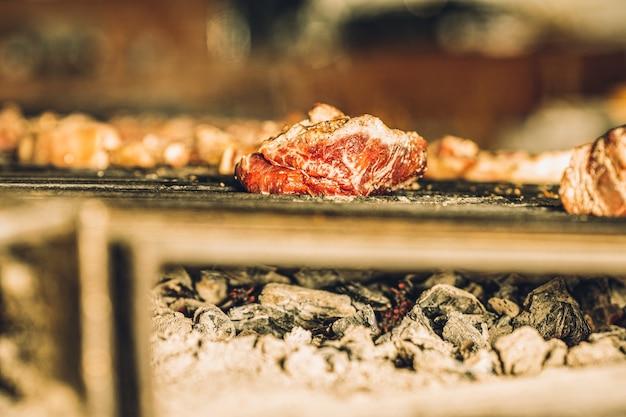 Кусочки сырого мяса медленно готовятся на гриле в ресторане.