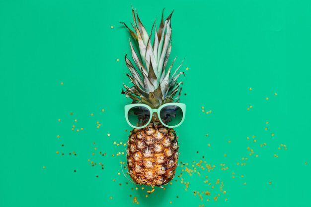 Raw pineapple with golden glitter. flat lay tropical concept