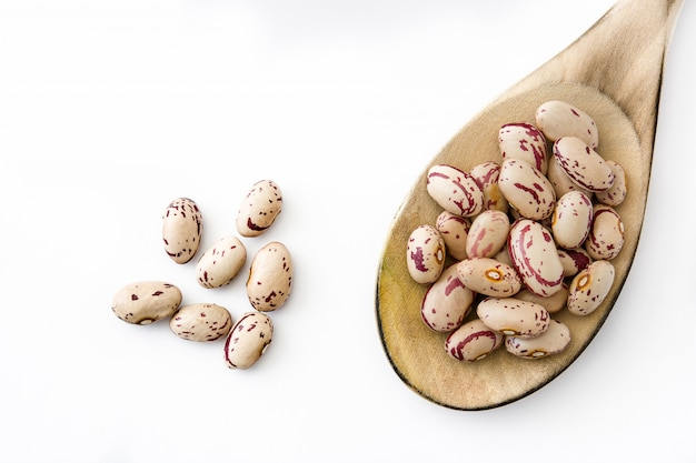 Raw pinto beans with wooden spoon isolated  top view