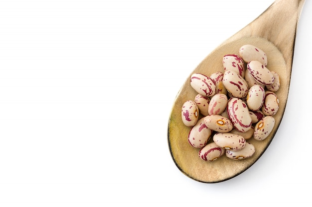 Raw pinto beans in wooden spoon isolated on white surface top view copy space