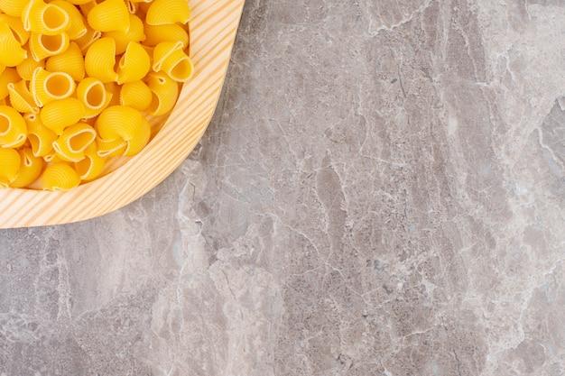 Сырые макароны для трубок на деревянной тарелке, на мраморной поверхности
