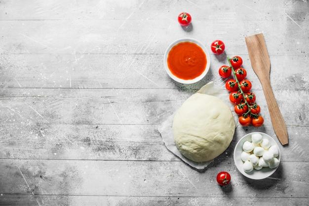 Сырая пицца. тесто с томатной пастой и моцареллой в мисках. на белом деревянном фоне