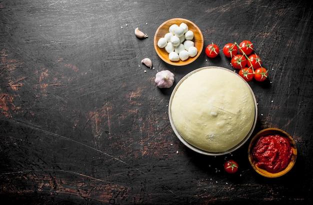 Сырая пицца. тесто с томатной пастой, моцареллой и помидорами черри. на темном деревенском фоне