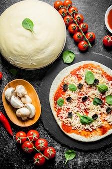 Сырая пицца. тесто с томатной пастой, грибами, оливками и перцем чили. на темном деревенском фоне