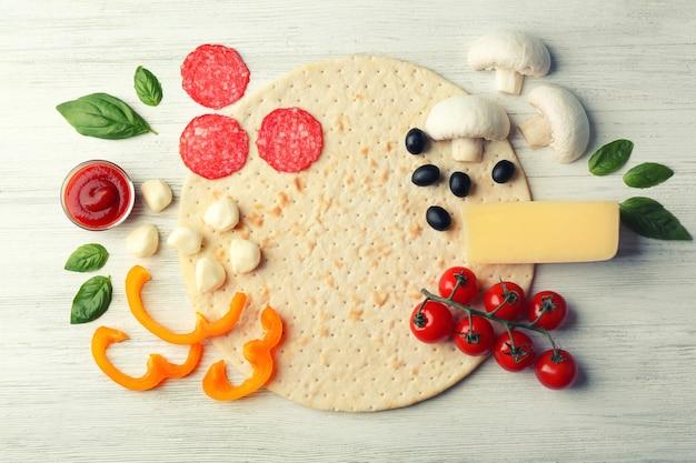 木製の背景、上面図の生ピザ食材