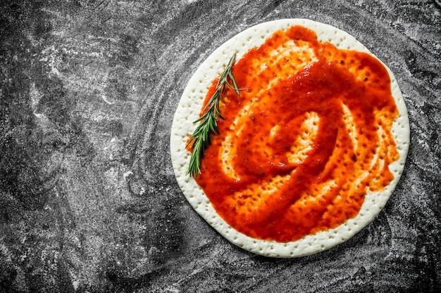 Сырая пицца. тесто для пиццы с томатной пастой. на деревенском фоне