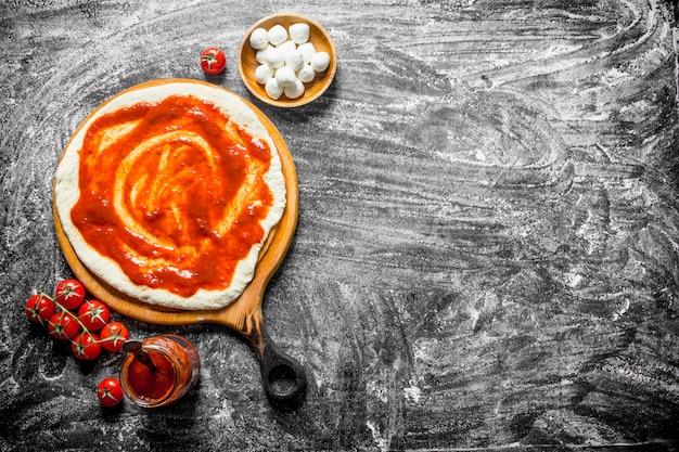 Сырая пицца. раскатанное тесто с томатной пастой, моцареллой и свежими помидорами. на деревенском фоне