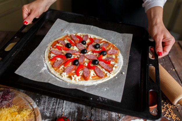 Raw pizza with ingredients on baking tray