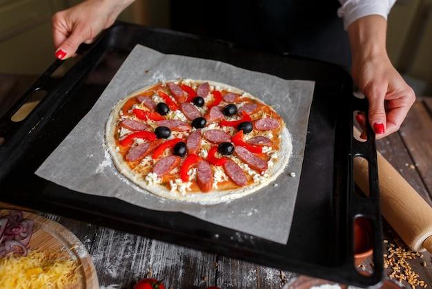 ベーキングトレイに材料を入れた生ピザ