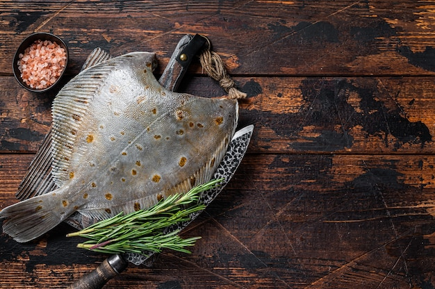 Raw plaice flatfish fish on butcher board with knife. dark wooden background. top view. copy space.